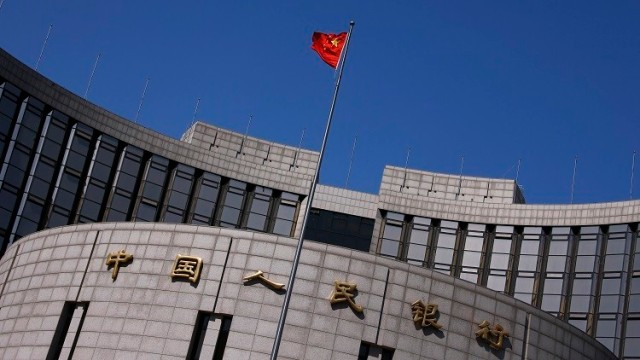 A Chinese national flag flutters outside the headquarters of the People's Bank of China, the Chinese central bank, in Beijing, April 3, 2014. Beijing's attack on yuan speculators has proven extraordinarily successful, so much so that traders no longer see it as a short-term intervention but a deeper market shift that has now gained a self-reinforcing momentum. That's bad news for speculators still holding onto bullish yuan positions. And for the People's Bank of China (PBOC), the risk is it has unleashed bearish forces it may not be able to rein in, souring enthusiasm for the yuan and complicating the push to increase the international adoption of the currency. To match Analysis CHINA-YUAN/    Picture taken April 3, 2014. REUTERS/Petar Kujundzic (CHINA - Tags: BUSINESS) - RTR3NRTO