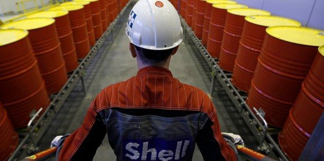 An employee stands in front of lines of oil barrels at Royal Dutch Shell Plc's lubricants blending plant in the town of Torzhok, north-west of Tver, November 7, 2014. Picture taken November 7, 2014. REUTERS/Sergei Karpukhin (RUSSIA - Tags: BUSINESS INDUSTRIAL) - RTR4FWLJ